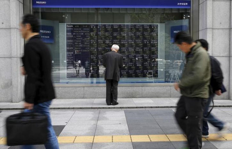 A man looks at a stock quotation board outside a brokerage in Tokyo, Japan, April 18, 2016. Photo: Reuters