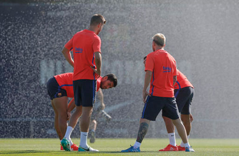 FC Barcelona s Luis Suarez, left, talks with Gerard Pique, second left, and Lionel Messi during a training session at the Sports Center FC Barcelona Joan Gamper in Sant Joan Despi, Spain, Saturday, Aug. 13, 2016.