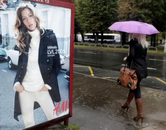 A woman walks past a H&M advertisement in Riga September 25, 2013. REUTERS