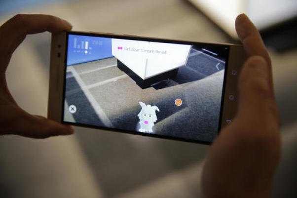 Sam Vang demonstrates playing with a virtual pet on the new Phab2 Pro phone at the Lenovo Tech World event, Thursday, June 9, 2016, in San Francisco. AP